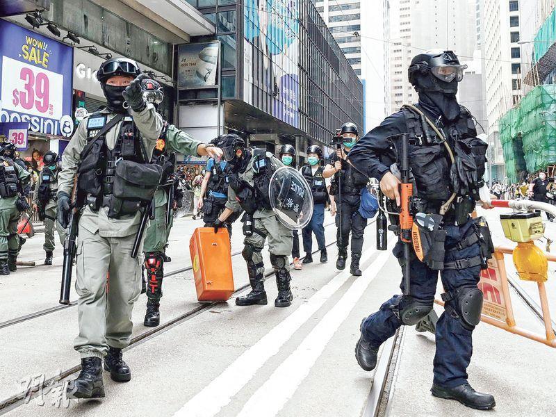 警方曾表示速龍小隊的戰術裝束不被視為警隊制服,其後規定速龍警員展示「Alpha ID」,防暴警員以「藍卡」展示新的行動呼號。資深大狀潘熙陳辭時稱,警方曾於去年11底修改警例,暫時豁免警員展示警員編號的規定。圖為上月27日中環和你lunch,防暴警員(左)和速龍隊員(右)清理路障。(資料圖片)