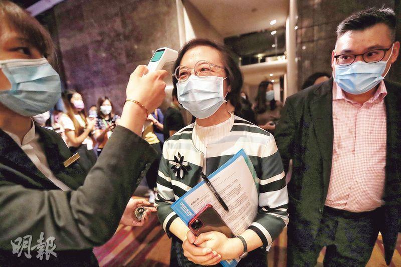 食物及衛生局長陳肇始(中)昨出席禁煙活動,進場前由工作人員量度體溫。圖右為吸煙與健康委員會主席鄺祖盛。(李紹昌攝)