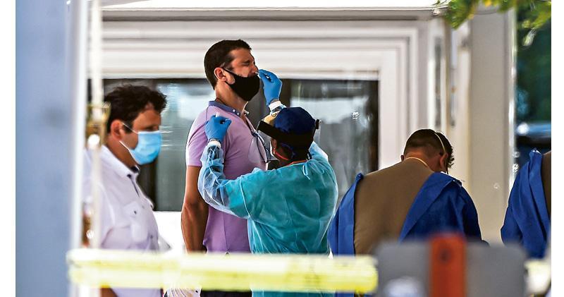 在佛羅里達州邁阿密海灘市,周三設有可供民眾免預約和駕車通過時採集樣本的檢測站,以助對抗新冠疫情。圖為一名男子由醫護人員採集鼻腔樣本。(法新社)
