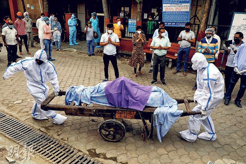 在新德里一個火葬場,上周三有身穿防護衣的醫療人員用木板車運送新冠病毒感染者的屍體。(路透社)
