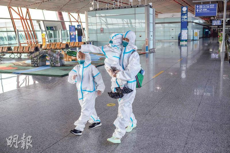 身穿全套防護服的乘客昨日正前往北京首都國際機場三號航站樓。因疫情關係,航站樓內旅客稀少。(法新社)