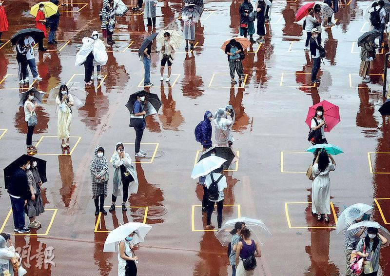 日本東京迪士尼因新冠疫情關閉多個月後重開,周三有民眾冒雨在樂園入口為保持社交距離而劃設的方格內排隊。(路透社)
