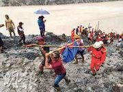 在緬甸帕敢塌山泥現場,昨有救援人員和民眾合力抬走死難者遺體。當局昨日已找到162具屍體,死亡人數相信會再增加。(路透社)