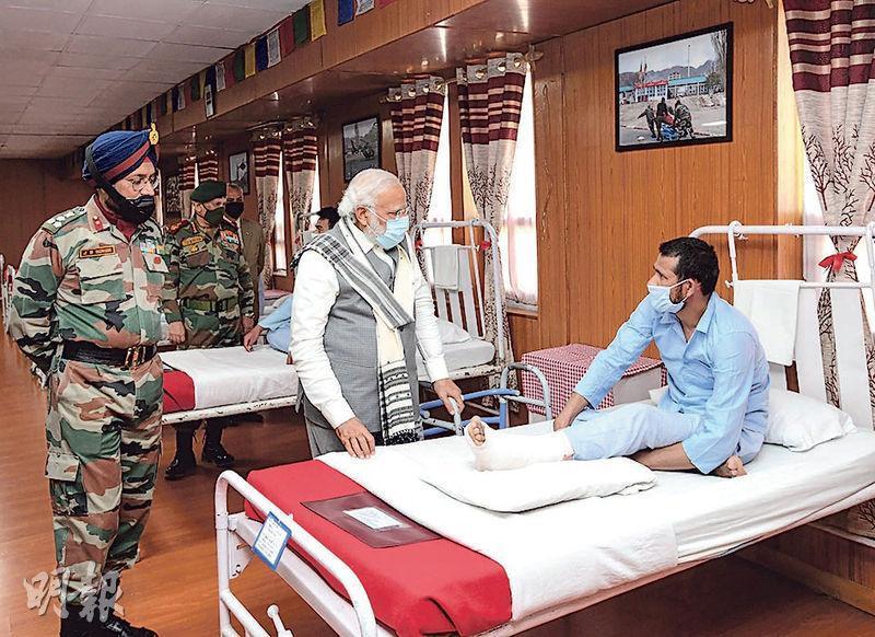印度總理莫迪(中)3日視察中印邊境拉達克地區,並在軍方醫院探望傷兵。(路透社)