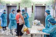 確診男患者居住的坪石邨玉石樓,管理大廈人員昨日在電梯大堂,向居民派發採集深喉唾液樣本檢測瓶。(任蕙山攝)