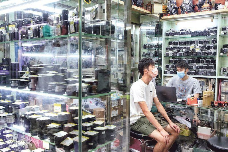 尖沙嘴「好友相機」店東何先生(右)表示,他們聘用一名員工,為店舖開拓網購業務,但稱疫情持續,看不到前景,認為保就業計劃只能暫時令僱主不裁員,並非治本之法。(曾憲宗攝)