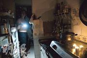 大廈多次停電,求助無援,停電期間嚴先生在家中只能靠點起蠟燭及手機燈光照明。(蔡方山攝)