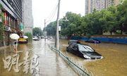 湖北汛情告急,長江湖北段水位全線上漲,該省有1081座水庫超過警戒上限。圖為7月6日上午,武漢市洪山區虎泉街保利華都小區外的街道積水嚴重,私家車浸在水中。(中新社)