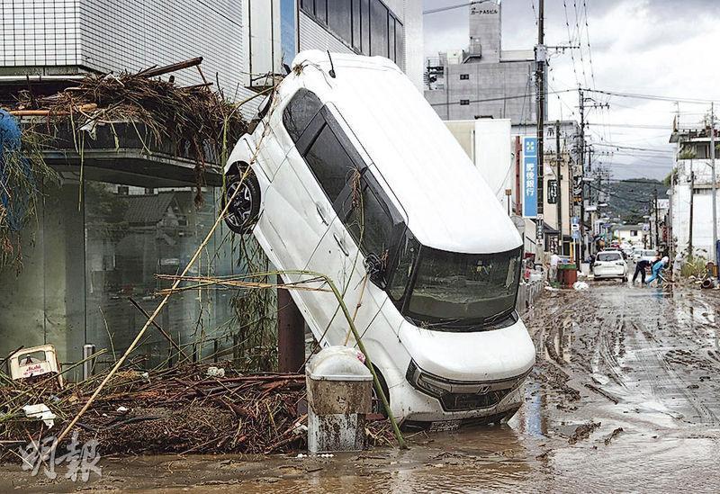 日本熊本縣人吉市由暴雨引發的水災周一消退,一輛被洪水冲來的汽車斜倚於一幢樓房外。(路透社)
