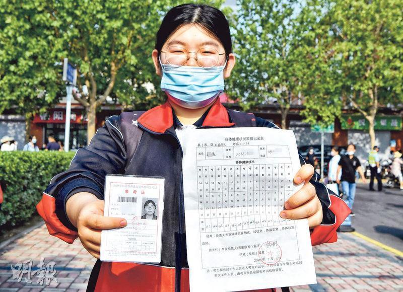 2020年高考昨天開鑼,河北石家莊一考場外,一名考生展示准考證和14天的體溫監測記錄表。(中新社)