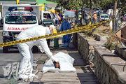 在玻利維亞爆發新型冠狀病毒肺炎疫情的科恰班巴,周一有人在街頭暴斃,穿著防護衣的法醫人員到場抽取死者樣本。(路透社)
