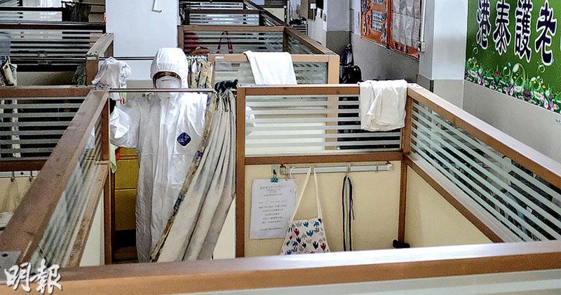 身穿全套保護衣物的清潔人員,昨日下午到爆疫的慈雲山港泰護老院地下的院舍清潔。(賴俊傑攝)