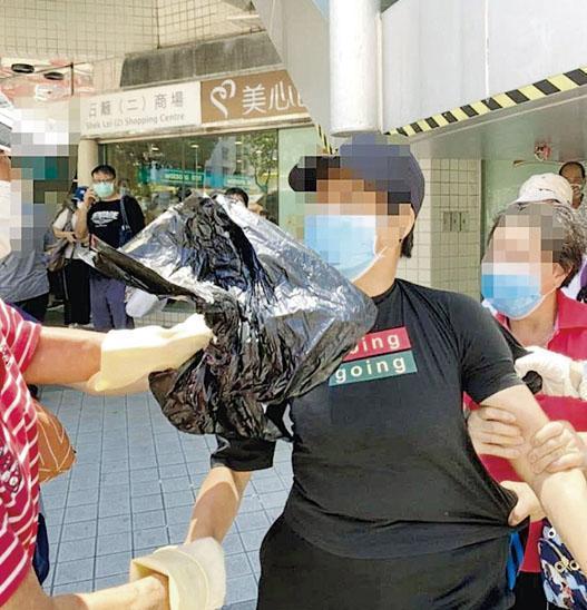 涉嫌向義工潑淋漂白水的女子(黑衫)即場被制服,其後由警方帶署扣查。(全港社區抗疫連線提供)