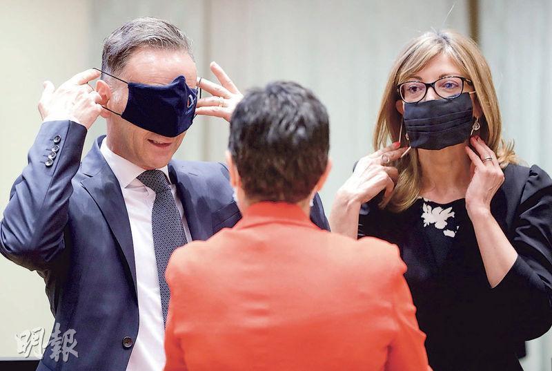 歐盟外長昨在布魯塞爾開會,會前德國外長馬斯(左)開玩笑將口罩遮蔽眼睛,身旁的保加利亞外長扎哈里埃娃(右)則正規地戴上口罩。(法新社)