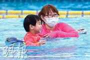 日本疫情近日反彈,民眾加強防疫。圖為東京一名母親昨日戴上口罩跟兒子在泳池耍樂。(法新社)