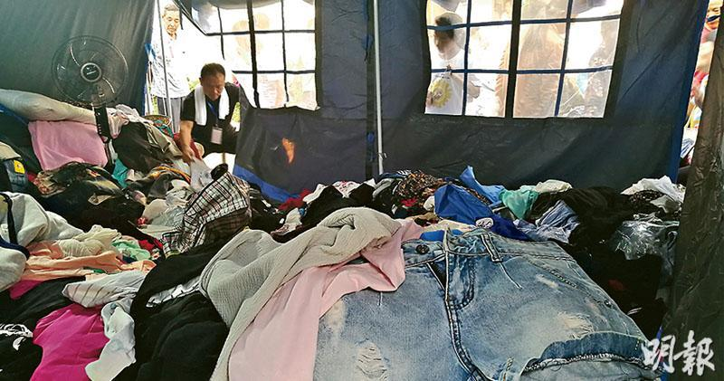江西永修縣民眾為災民捐出大批衣物,堆放在湖東學校的帳篷裏,供災民挑選。(鄭海龍攝)