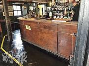 英國英格蘭的酒吧7月4日獲准重新開門營業,但仍維持社交距離強制措施。位於康沃爾郡聖賈斯特(St Just)的The Star Inn的酒吧東主為確保顧客守法,特意在酒吧的吧枱前安裝電圍欄。該電欄通常不會通電,不過效果不俗,成功阻止顧客靠近。(路透社)