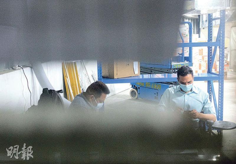 本報記者昨晚到太平工業園3樓觀察,大門已關上,縫隙間見有兩名保安守門,亦放有多箱貨物。記者拍照後被保安趕走。(林靄怡攝)