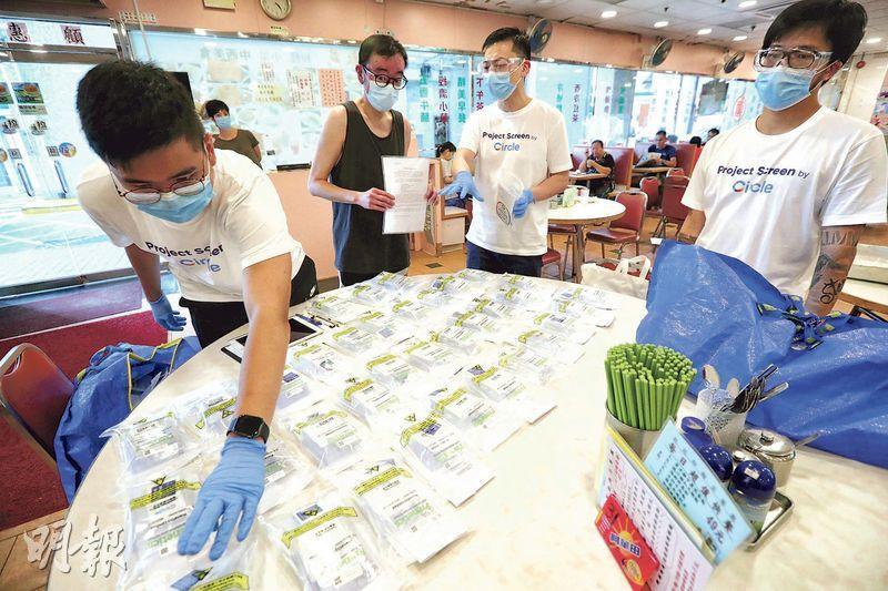 政府正為食肆員工驗病毒,負責的檢測公司昨天在黃大仙斧山道的食肆派發樣本瓶。(李紹昌攝)