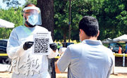 在美國加州洛杉磯一個新型冠狀病毒檢測點,全副安全裝備的義工上周五(17日)向未經預約來接受測試的人士,展示二維條碼供手機掃描。(法新社)