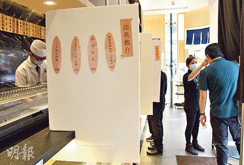 政府延長食肆晚市限制,對食肆生意有影響。日式食店「立鮨 」負責人楊小姐(右二)表示,現時疫情嚴重,認為食肆「晚六朝五」禁堂食措施合理,相信對禁止人群在餐廳聚集有幫助。圖為她替顧客量體溫。(朱安妮攝)