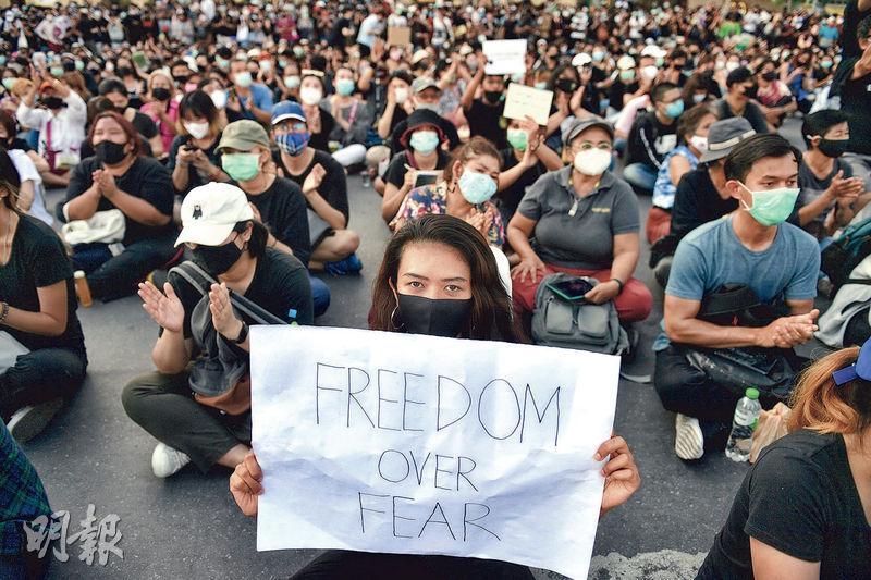 泰國曼谷前天爆發自2014年軍事政變以來的最大型示威,有示威者手持「克服恐懼的自由」標語牌表達訴求。(路透社)