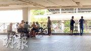 本報記者昨午到沙田沙角邨觀察,在中銀分行對開有蓋行人通道發現10多名男子聚賭,部分人無戴口罩或將口罩拉到下巴。(梁銘康攝)