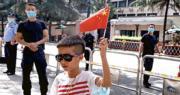 美國駐成都總領事館須今日關閉。圖為昨日一名男孩在領事館對面的人行道上舉起一面五星紅旗。(路透社)