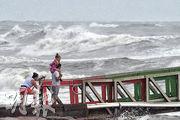 颶風「漢娜」前天吹襲美國得州,有民眾仍冒險到海邊觀潮。(路透社)