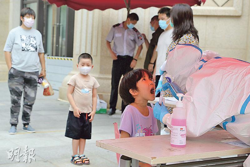 國家衛健委披露,26日內地新增確診病例61宗,為4月13日以來新高。圖為在疫情反彈的遼寧大連,一名醫務人員昨日為一名兒童採集深喉唾液樣本,以作病毒檢測。(法新社)
