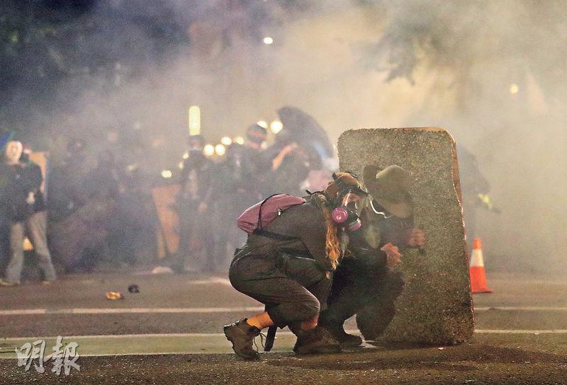 美國波特蘭市周一的反種族主義和反警暴示威中,有示威者在一片白茫茫的催淚煙下,手持盾牌躲藏。(路透社)