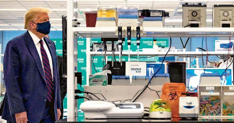 美國總統特朗普周一戴着口罩,參觀位於北卡羅萊納州一間研發新冠疫苗的實驗室。(法新社)