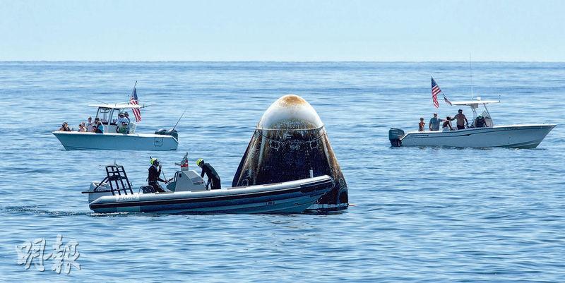 SpaceX「龍飛船」周日安全在墨西哥灣海面「濺落」後,支援隊伍上前檢查,也吸引好奇遊客圍觀。(路透社)
