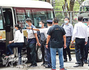 「內地核酸檢測支援隊」7名先遣隊成員昨午到訪大埔太平工業園的華昇診斷中心,遇上區議員及市民抗議,先遣隊成員離開時由警員護送上車。(李紹昌攝)