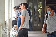 本報昨午在金鐘連接海富中心及統一中心的行人天橋上,在半小時內發現約20人除下口罩吸煙,未見警察執法。圖左方的灰衣男子及兩名友人結伴吸煙聊天,他們均除下口罩。(鍾林枝攝)