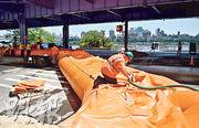 紐約市周一有工作人員在曼哈頓下城架起防洪工具,為風暴做準備。(法新社)