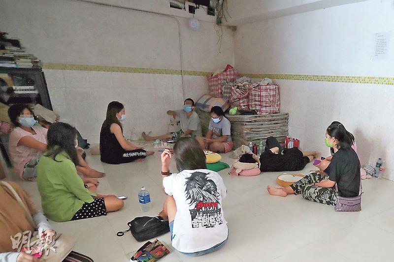 記者昨午到北角英皇道珠璣大廈2樓A室一所外傭宿舍,見內有10多名外傭坐在地上休息,單位內侷促,幾乎沒有家具,只堆放了一疊牀墊。(李紹昌攝)