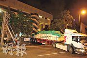 一輛寫有「華大基因火眼實驗室援港物資」的貨櫃車昨晚現身西環中山紀念公園體育館,有工人將車上木箱搬入體育館內,館外有警員戒備。(伍浦鋒攝)