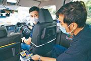 的士司機鍾先生(左)近日主動向八達通申請安裝流動收款機,他認為減少交收現鈔可降低感染新冠病毒風險,保障自己及乘客安全。(八達通提供)