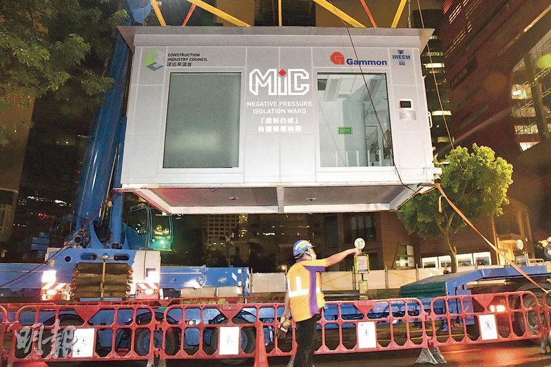 工人昨日凌晨將原位於九龍灣零碳天地的組裝合成負壓病房吊運往亞博館的「社區治療設施」。該設施由金門建築以貨櫃改裝而成,每組成本約200萬元。(蔡方山攝)