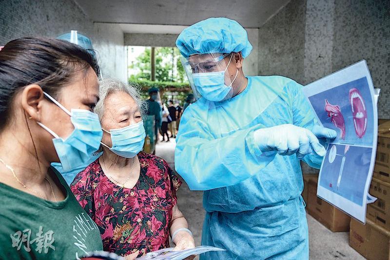 民政總署與東華三院人員昨到慈愛苑派發咽拭子採樣套裝和登記表格,並指示街坊如何「撩喉嚨」採樣。(賴俊傑攝)