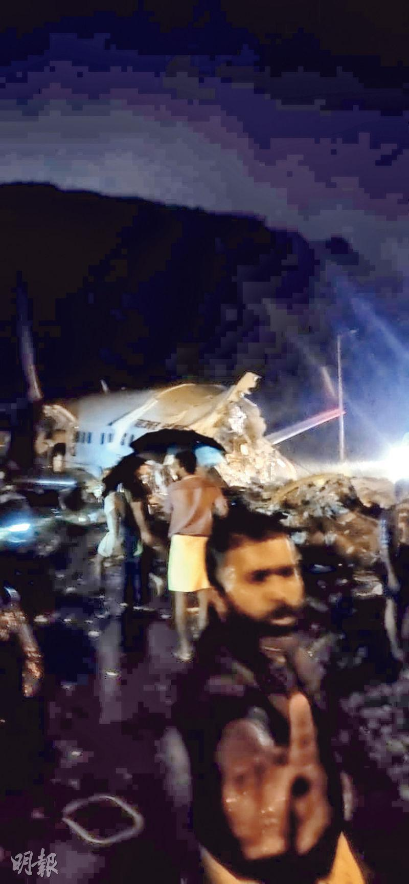 印度電視台畫面顯示客機斷開兩截,人們試圖拯救機上乘客。(網上圖片)