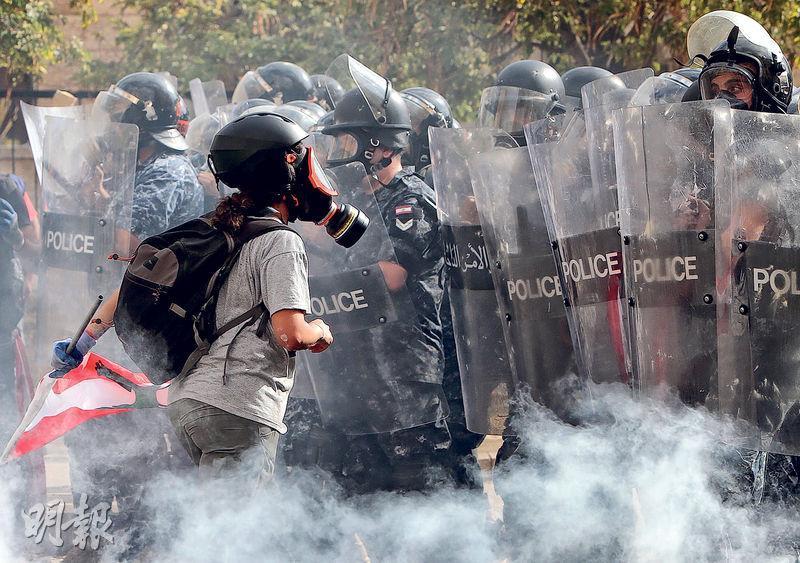 昨在貝魯特,防暴警察築起防線,阻止示威者前往國會。(法新社)