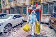 國家衛健委通報,內地上周六(8日)報告新增新冠肺炎15宗本地病例均在新疆自治區。圖為上周六,新疆烏魯木齊市一名志願者,幫助隔離區的民眾處理生活垃圾。(新華社)