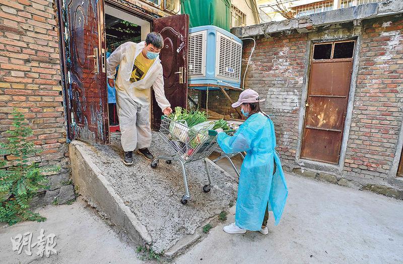 近日內地新增本土病例幾乎都發生在新疆烏魯木齊市。圖為8月8日,兩名義工將隔離區居民在網上採購的蔬菜運出社區蔬菜直銷點。(新華社)