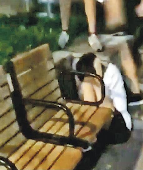 白衫少年雙手擋頭、蹲在地上,其身旁的童黨仍不斷向他拳打腳踢,更有人從高處以腳踩他的頭部。(網片截圖)