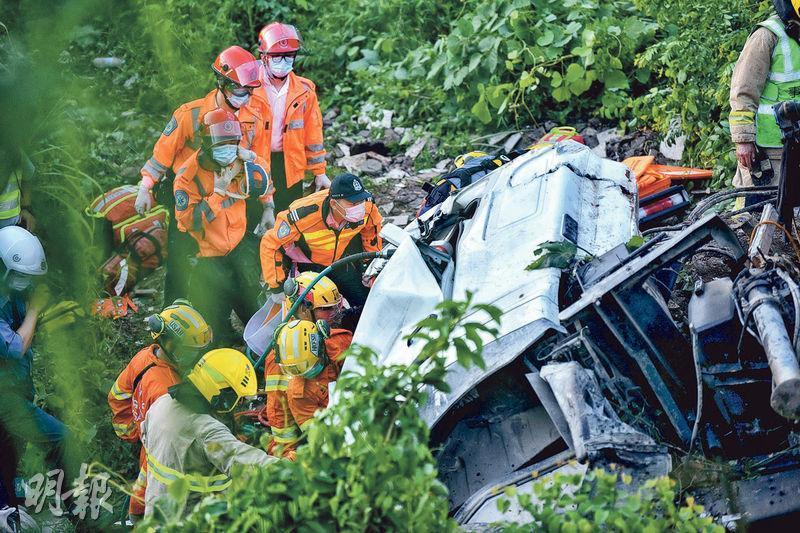 泥頭車失控衝下約20米山坡,繼而向右翻側,車頭嚴重損毁,司機被困車廂,拯救逾2小時始將他救出。(梁銘康攝)