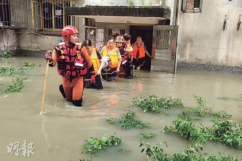 國家防汛總指揮部昨稱,今年洪澇災害對糧食安全不會有影響。圖為周三四川成都暴雨成災,有救援人員救出受困民眾。(新華社)