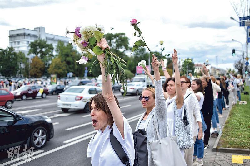 明斯克昨有婦女身穿白衣和手持鮮花,在路邊組成「人鏈」,抗議警暴。(法新社)