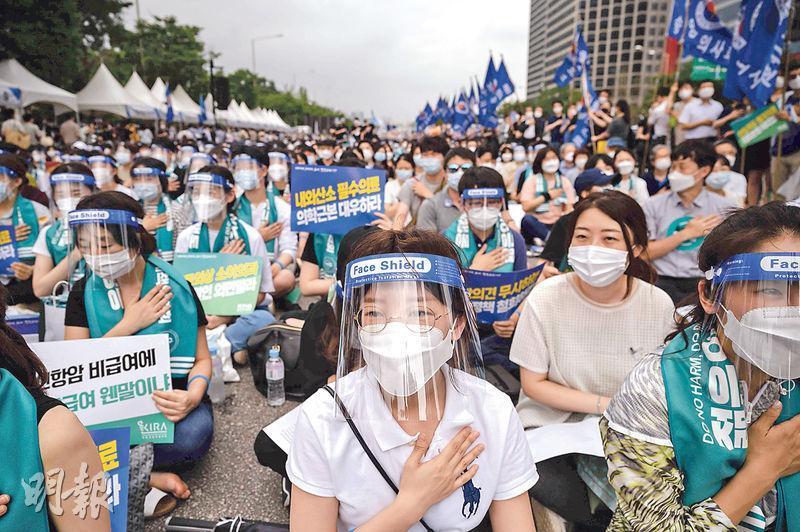 韓國醫生及醫科學生等昨日在首爾集會,抗議政府計劃增加每年醫科生收生。(法新社)